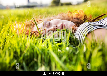 Portrait of redheaded young woman with eyes closed lying on meadow - Stock Photo