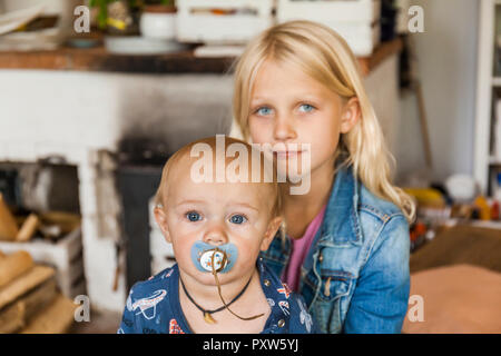 Portrait of girl with baby boy brother at home - Stock Photo