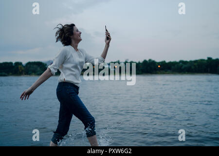 Laughing woman running at the riverside, using smartphone - Stock Photo
