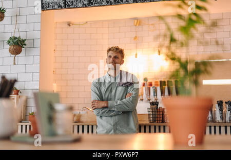 Young man working in his start-up cafe, portrait