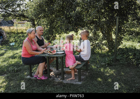 Grandparents spending time together with grandson and granddaughter in the garden eating watermelon - Stock Photo