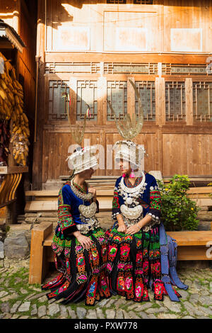 China, Guizhou, two smiling young Miao women wearing traditional dresses and headdresses - Stock Photo