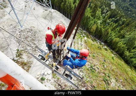 Germany, Bavaria, Garmisch-Partenkirchen, Zugspitze, installers working on goods cable lift - Stock Photo