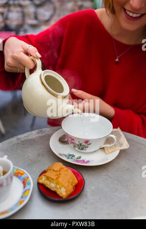 Smiling young woman pouring water into a cup at pavement cafe, partial view - Stock Photo