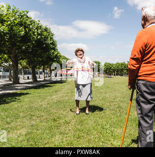 Senior watching elderly lady playing with a hoola hoop - Stock Photo