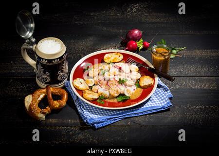 Bavarian veal sausage salad with roasted pretzel rolls, sweet mustard, pretzels, red radish and beer mug - Stock Photo