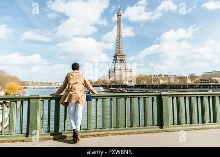 France, Paris, Female tourist looking towards the Eiffel tower and the Seine river - Stock Photo