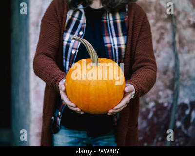 Woman's hands holding big pumpkin - Stock Photo