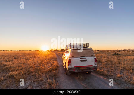 Botswana, Kalahari, Central Kalahari Game Reserve, off-road vehicle on gravel road at sunrise - Stock Photo