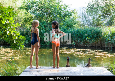 Two girls standing on jetty at a pond talking - Stock Photo