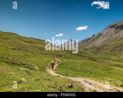 Switzerland, Lower Engadin, mountainbiker on path towards Uina gorge - Stock Photo