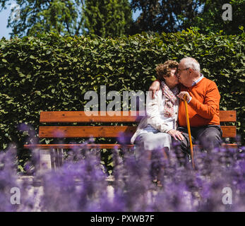 Senior couple sitting on bench in a park, kissing - Stock Photo