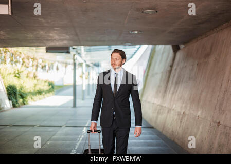 Businessman with rolling suitcase walking in underpass - Stock Photo