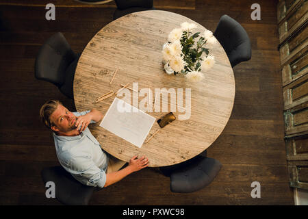 Mature man sitting at a round table, drawing with coloured pencils, overhead view - Stock Photo