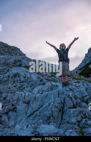 Austria, Salzburg State, Loferer Steinberge, boy on a hiking trip cheering in the mountains - Stock Photo