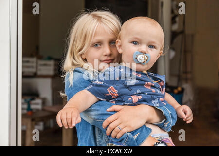 Portrait of girl holding baby boy brother at home - Stock Photo