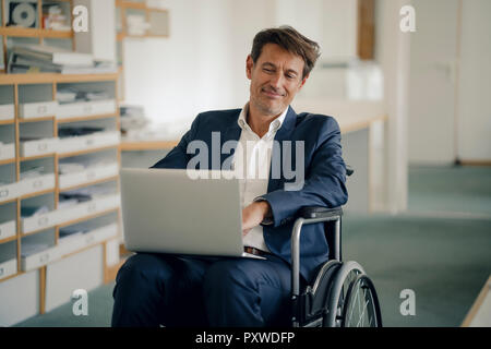 Businessman in wheelchair, using laptop in office - Stock Photo