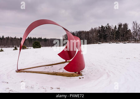 Whales Tail, a red aluminum sculpture by Miriam Nelson, punctuates winter landscape at the Stone Quarry Hill Art Park in the town of Cazenovia in Madi - Stock Photo