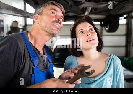 Client and mechanic checking defects in the car - Stock Photo