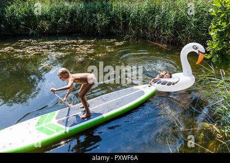 Two girls in a pond with inflatable pool toy in swan shape and SUP board - Stock Photo