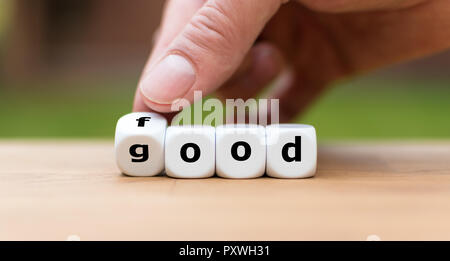 Hand is turning a dice and changes the word good to food - Stock Photo