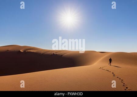 Africa, Namibia, Namib desert, Naukluft National Park, tourist walking on dune - Stock Photo