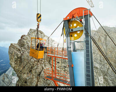 Germany, Bavaria, Garmisch-Partenkirchen, Zugspitze, installers working on goods cable lift in a work cage - Stock Photo
