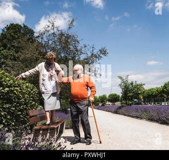 Senior couple having fun in the park, senior man helping womn to balance on bench - Stock Photo