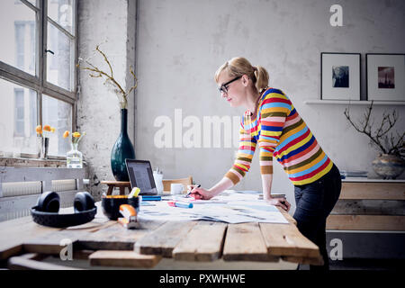 Woman working at desk in a loft - Stock Photo