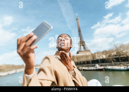 France, Paris, Woman taking a selfie with the Eiffel tower in the background - Stock Photo