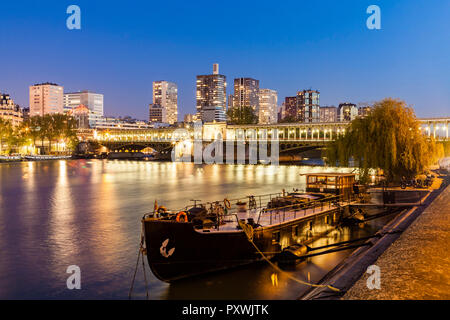 France, Paris, Pont de Bir-Hakeim, Seine river, modern high-rise buildings at blue hour - Stock Photo