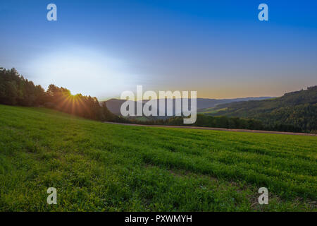 Colorful bright sunrise rural panoramic landscape image with a wide view over fields,forest,hills and foggy valleys towards the horizon and a blue sky - Stock Photo