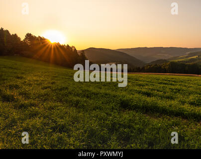 Warm colored bright golden epic sunrise rural panoramic landscape image with a wide view over fields,forest,hills and valleys towards the horizon - Stock Photo