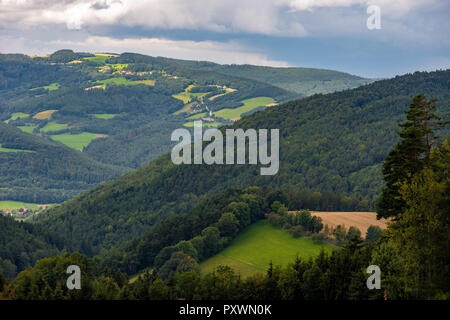 Color rural summer landscape image of an idyllic farmland countryside with clouds in the sky and a downhill view over fields, forest and valleys - Stock Photo