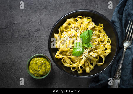 Tagliatelle pasta with pesto sauce and parmesan. - Stock Photo