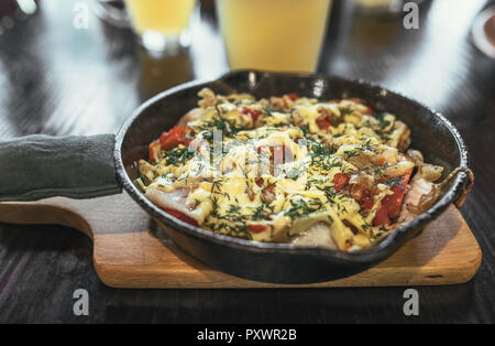Frying pan with meat, vegetables and potatoes under melted cheese with golden beer - Stock Photo