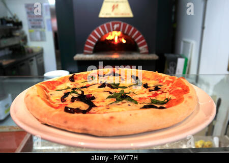 ham, mushrooms, black olives & artichokes Pizza, cooked in a traditional wood fired pizza oven - Stock Photo