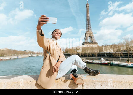 France, Paris, Woman sitting on bridge over the river Seine with the Eiffel tower in the background taking a selfie - Stock Photo