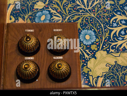 Four brass, domed vintage electrical light switches arranged in a square on bright wallpaper of blue and gold flowers and gold swirls at Lanhydrock. - Stock Photo