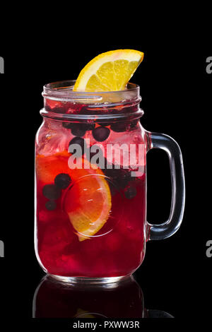 Cocktail with black currant and vodka in mason jar mug isolated on black - Stock Photo