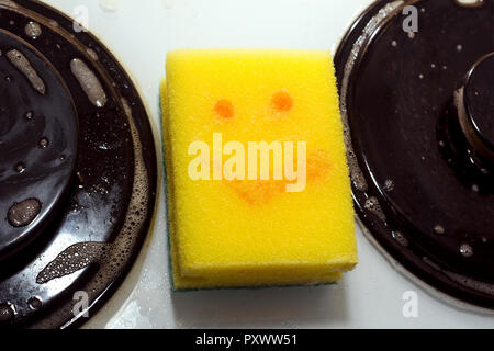 yellow sponge with painted smile, for dishes on dirty gas stove - Stock Photo
