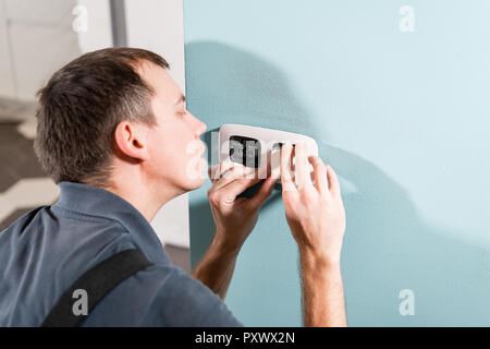 A young electrician installing an electrical socket in a new house. - Stock Photo