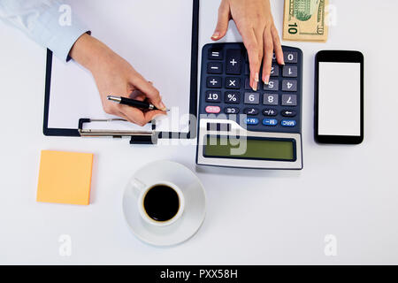 Calculating expenses. High angle of young woman calculating invoice at desk. Woman counting money at the table - Stock Photo