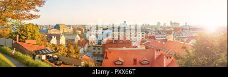 panoramic image of female tourist looking at Zagreb city center view with beautiful old buildings at sunset on warm fall day, Croatia - Stock Photo