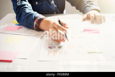 Startup business woman working with business documents on office table with  graph financial diagram. - Stock Photo