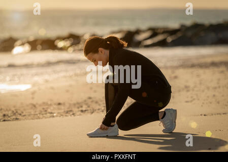 woman jogger adjusting her shoes before running on the beach - Stock Photo