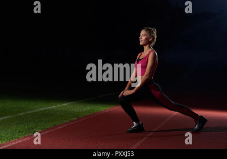 Sporty and pretty girl in stylish black and pink sportswear stretching on stadium at night after running. Woman training for first marathon, doing exercise from yoga. Concept of sport activity. - Stock Photo