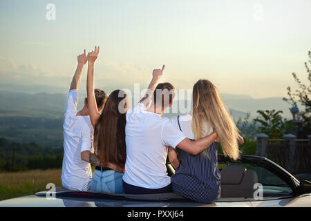 Two couples sitting on cabriolet and admiring landscapes and amazing view. Men putting arms round girls' waists and holding hands up. Friends enjoying summertime and journey by car. - Stock Photo
