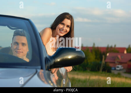 Front view of handsome man sitting in driver's seat in cabriolet and driving. Charming beautiful young woman with chestnut hair looking out car at camera and smiling. Couple traveling by car. - Stock Photo