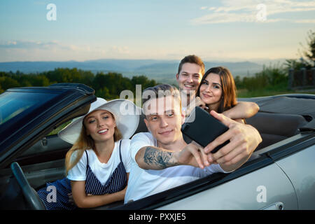 Two beautiful couple sitting in cabriolet and making selfie. Handsome boy holding phone and friends looking at gadget. Company spending summertime together, traveling by car. - Stock Photo